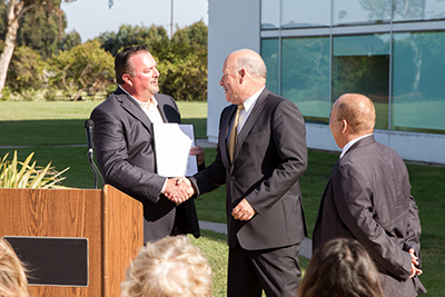 "Larry Palochik (left), senior vice president of member solutions for the California and Nevada Credit Union Leagues, recognizes Ventura County CU by welcoming the credit union's CEO, Joe Schroeder, to speak at the ""Juntos Avanzamos"" designation ceremony."