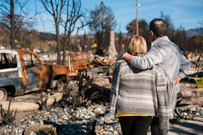 Image of couple in front of burned, destroyed home