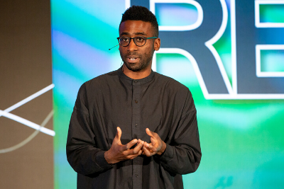 Violinist and composer Kai Kight speaks during the opening general session for REACH on Monday afternoon.