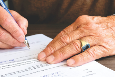 Image of hand signing documents