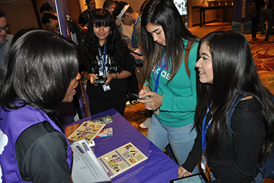 """L-R: Amistad High School students Cheyenne Chapa, 16, and Angelina Moran, 16, learn about budgeting and making real-life financial choices at the """"Bite of Reality"""" event before the REACH 2017 annual convention."""